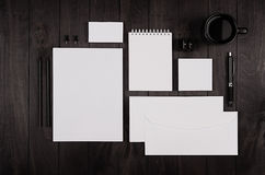 Espacio de funcionamiento oscuro de la elegancia con la libreta, el papel con membrete, la tarjeta de visita, la taza de café y e Fotografía de archivo