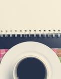 Espacio de la copia del cuaderno con la taza de café abajo Fotografía de archivo