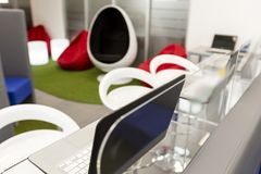 Espacio de oficina moderno con los escritorios y los ordenadores portátiles; espacio del salón en el fondo foto de archivo libre de regalías