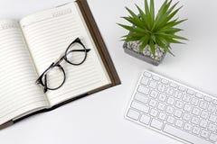 Espacio de trabajo blanco mínimo con el teclado, el cuaderno y los vidrios fotos de archivo