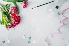 Espacio de trabajo con el cuchillo de paleta, la pintura de la lona, la flor del tulipán y el mosaico en backround gris imagen de archivo libre de regalías