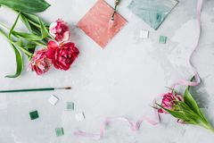 Espacio de trabajo con el cuchillo de paleta, la pintura de la lona, la flor del tulipán y el mosaico en backround gris imagen de archivo