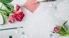 Espacio de trabajo con el cuchillo de paleta, la pintura de la lona, la flor del tulipán y el mosaico en backround gris foto de archivo