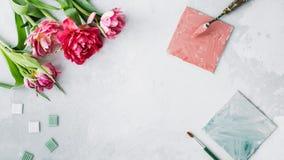 Espacio de trabajo con el cuchillo de paleta, la pintura de la lona, la flor del tulipán y el mosaico en backround gris fotos de archivo