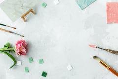Espacio de trabajo con el cuchillo de paleta, la pintura de la lona, la flor del tulipán y el mosaico en backround gris fotos de archivo libres de regalías
