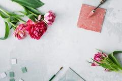 Espacio de trabajo con el cuchillo de paleta, la pintura de la lona, la flor del tulipán y el mosaico en backround gris imágenes de archivo libres de regalías