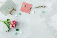 Espacio de trabajo con el cuchillo de paleta, la pintura de la lona, la flor del tulipán y el mosaico en backround gris foto de archivo libre de regalías