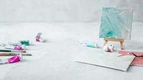 Espacio de trabajo con el cuchillo de paleta, la pintura de la lona y los tubos de la pintura en backround gris foto de archivo libre de regalías