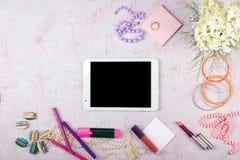 Espacio de trabajo con el ordenador, hortensias del ramo, tablero Complementos del ` s de las mujeres aislados en fondo rosado pl Foto de archivo