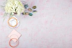 Espacio de trabajo con el ordenador, hortensias del ramo, tablero Complementos del ` s de las mujeres en fondo rosado plano Fotografía de archivo