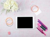 Espacio de trabajo con el ordenador, hortensias del ramo, tablero Complementos del ` s de las mujeres en fondo rosado plano Imagen de archivo libre de regalías