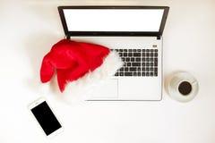 Espacio de trabajo con el regalo del ordenador portátil y de la Navidad y el sombrero de santa en la endecha blanca del plano del Imágenes de archivo libres de regalías