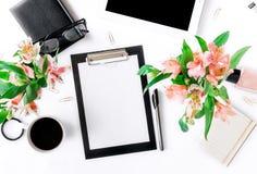 Espacio de trabajo con el tablero, los accesorios de la oficina, el café y el ramo Imagen de archivo libre de regalías