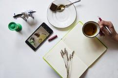 Espacio de trabajo con la libreta, taza de t? en un fondo blanco Endecha plana, escritorio del escritorio de oficina de la visi?n fotografía de archivo