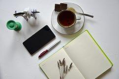 Espacio de trabajo con la libreta, taza de t? en un fondo blanco Endecha plana, escritorio del escritorio de oficina de la visi?n fotografía de archivo libre de regalías