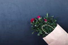 Espacio de trabajo con las flores color de rosa en una bolsa de papel en fondo negro Imágenes de archivo libres de regalías