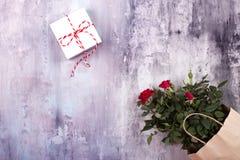 Espacio de trabajo con las flores color de rosa, regalo, bolsa de papel Visión superior, endecha plana Imagen de archivo