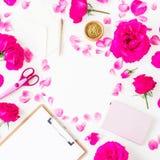 Espacio de trabajo con las rosas, pétalos y tablero, cuaderno y accesorios rosados en el fondo blanco Endecha plana, visión super Imágenes de archivo libres de regalías