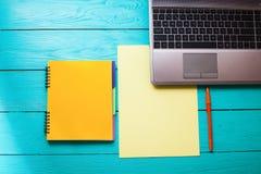 Espacio de trabajo con los accesorios del negocio en la tabla de madera azul Visión superior Mofa para arriba Imagen de archivo