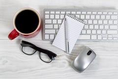 Espacio de trabajo con tecnología y café en la mesa blanca Fotos de archivo libres de regalías