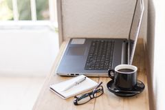 Espacio de trabajo con un ordenador portátil, café, el cuaderno, y vidrios foto de archivo libre de regalías