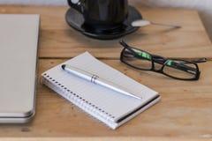 Espacio de trabajo con un ordenador portátil, café, el cuaderno, y vidrios fotos de archivo