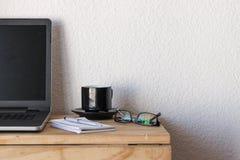 Espacio de trabajo con un ordenador portátil, café, el cuaderno, y vidrios fotografía de archivo