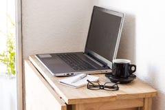 Espacio de trabajo con un ordenador portátil, café, el cuaderno, y vidrios imagen de archivo libre de regalías