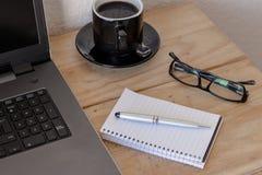 Espacio de trabajo con un ordenador portátil, café, el cuaderno, y vidrios imagenes de archivo