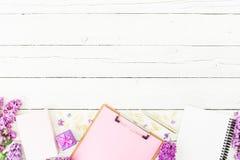 Espacio de trabajo de Minimalistic con el tablero, el cuaderno, la pluma, la lila, la caja del anillo y los accesorios en el fond Foto de archivo libre de regalías