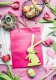Espacio de trabajo de Pascua con el conejo y los tulipanes en color rosado Flores y accesorios para las decoraciones de pascua qu Imágenes de archivo libres de regalías