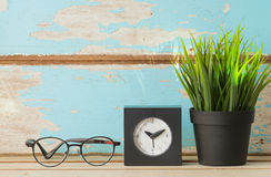 Espacio de trabajo decorativo con el ove del pote de los vidrios, del reloj y de la hierba verde Foto de archivo