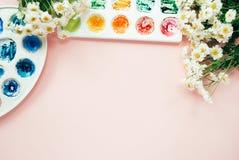 Espacio de trabajo del artista con la manzanilla blanca del ramo, paletas de la acuarela en un pálido - fondo en colores pastel r Imagen de archivo libre de regalías