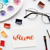 Espacio de trabajo del artista Redacte agradable escrito en estilo de la caligrafía, cubetas de la acuarela y paleta en un fondo  Foto de archivo libre de regalías