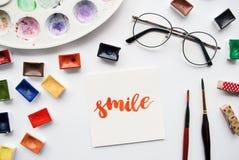 Espacio de trabajo del artista Redacte la sonrisa escrita en estilo de la caligrafía, cubetas de la acuarela y paleta en un fondo Fotos de archivo libres de regalías
