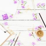 Espacio de trabajo del Blogger con el tablero, el cuaderno, las flores rosadas y los accesorios en fondo de madera rústico Concep Imagenes de archivo