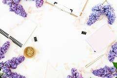 Espacio de trabajo del Blogger con el tablero, la lechería, el sobre, las flores de la lila y los accesorios en el fondo blanco E Fotos de archivo