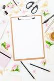 Espacio de trabajo del Blogger o del freelancer con el tablero, el cuaderno, las flores y los accesorios en el fondo blanco Conce Fotos de archivo
