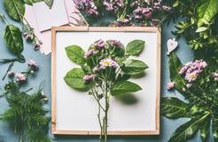 Espacio de trabajo del florista Centro de flores con las ramas verdes y las flores rosadas foto de archivo