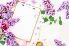 Espacio de trabajo del Freelancer o del blogger con el tablero, el cuaderno, el sobre, la lila, y los tulipanes en el fondo blanc Imágenes de archivo libres de regalías
