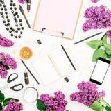 Espacio de trabajo del Freelancer o del blogger con el tablero, el teléfono móvil, el cuaderno, el lápiz labial, la lila y los ac Foto de archivo libre de regalías
