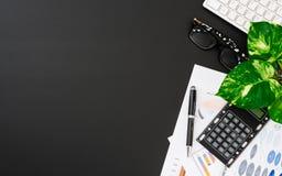 Espacio de trabajo de escritorio puesto plano de la oficina del teclado inal?mbrico, gr?fico y cartas del informe, pluma, calcula foto de archivo libre de regalías