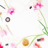 Espacio de trabajo femenino casero con el tablero, el cuaderno, las flores rosadas y los accesorios en el fondo blanco Endecha pl Fotografía de archivo