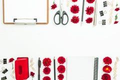 Espacio de trabajo femenino con el tablero, el cuaderno, las flores rojas y los accesorios en el fondo blanco Marco de la fronter Imagen de archivo libre de regalías