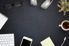 Espacio de trabajo de la oficina con el teclado de ordenador, teléfono elegante, taza de café, auriculares, vidrios, libreta, pla Imagen de archivo libre de regalías