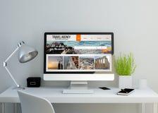 Espacio de trabajo limpio moderno con sitio web de la agencia de viajes en la pantalla Imagen de archivo