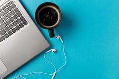 Espacio de trabajo m?nimo con el ordenador port?til, la taza de caf? y los auriculares foto de archivo libre de regalías