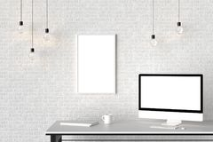 Espacio de trabajo moderno con el marco vacío aislado en la pared de ladrillo y la ISO Fotografía de archivo libre de regalías