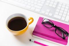 Espacio de trabajo moderno de la oficina con café, el ordenador y los vidrios Fotos de archivo libres de regalías