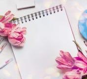 Espacio de trabajo para mujer de la primavera con pálido - tulipanes rosados, cuaderno o sketchbook y marcadores coloridos del ce Foto de archivo libre de regalías
